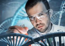 Young scientist mixing reagents in glass flask in clinical laboratory. Handsome scientist making research over dna molecule structure Royalty Free Stock Photography