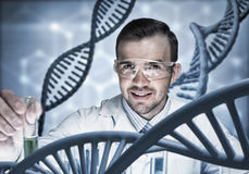 Young scientist mixing reagents in glass flask in clinical laboratory. Handsome scientist making research over dna molecule structure Stock Images