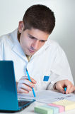 Young scientist reads fresh publication Royalty Free Stock Photography