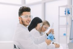 Young scientist shows a beaker with liquid. Science and health royalty free stock image