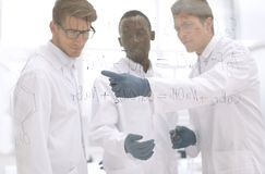 Young scientist shows a finger on the glass Board. Concept of education stock image
