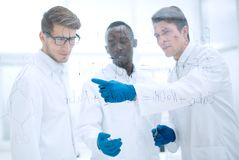 Young scientist shows a finger on the glass Board stock image