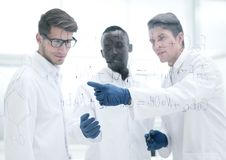 Young scientist shows a finger on the glass Board. Concept of education royalty free stock photography