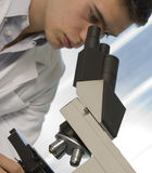 Young scientist watching inside a microscope Royalty Free Stock Image