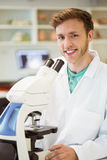 Young scientist working with microscope Royalty Free Stock Photos