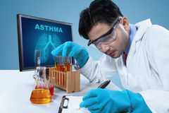 Young scientist working with test tubes. Picture of an Asian scientist writing a report, while working with a computer and test tubes on the desk Stock Photo