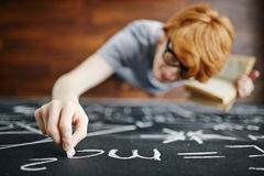 Young Scientist Writing on Blackboard in Class Royalty Free Stock Images