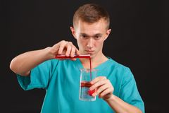 Man scientist pouring liquid from a test tube into a flask close-up on a black background Stock Photos
