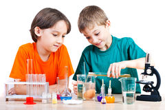 Young scientists. Two little boys doing biochemistry research at the lab. Isolated on white Stock Photos