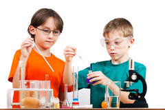 Young scientists. Two little boys doing biochemistry research at the lab. Isolated on white Royalty Free Stock Image
