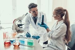 Young Scientists doing Research in Laboratory. Researchers wearing White Coats Gloves and Glasses examining Chemical Liquid Samples in Flasks and taking Notes Royalty Free Stock Images