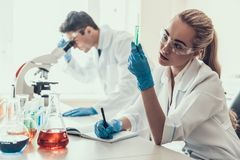 Young Scientists examining Samples in Laboratory. Female Researcher looking at Chemical Liquid Samples in Flasks while Male Scientist using Microscope Royalty Free Stock Photos