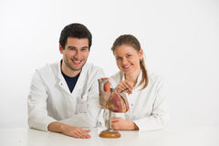 Young scientists with heart. Couple of young doctors, men and woman, with model of human heart Royalty Free Stock Images