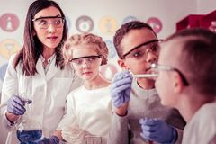 Elementary school group looking surprised on their classmate. Young scientists helping. Elementary school group looking surprised on their classmate during stock images