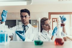 Young Scientists look at Sampes in Laboratory. Researchers wearing White Coats Gloves and Protective Glasses examining Chemical Liquid Samples in Flasks Royalty Free Stock Photos
