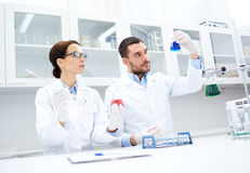 Young scientists making test or research in lab. Science, chemistry, technology, biology and people concept - young scientists with pipette and flask making test Royalty Free Stock Photography