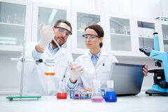 Young scientists making test or research in lab. Science, chemistry, technology, biology and people concept - young scientists with pipette and glass making test Stock Photos