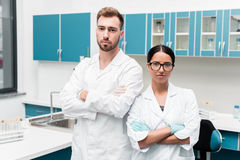 Young scientists in white coats standing with crossed arms and looking at camera in lab stock photo