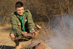 Young scout cooking his lunch over a fire Stock Images