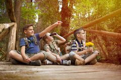 Young scouts sitting on old wooden bridge in the woods Royalty Free Stock Photo