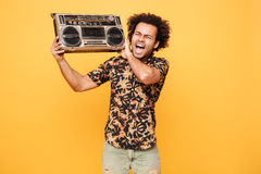 Young screaming african man standing with tape recorder Royalty Free Stock Photography