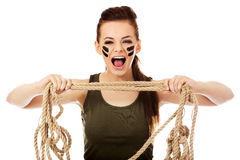 Young screaming soldier woman tugging a rope.  Royalty Free Stock Images