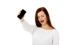 Young screaming woman shows broken touch screen mobile phone Royalty Free Stock Images