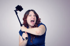 Young screaming woman with a stick for self. Royalty Free Stock Photo
