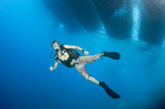 Young scuba diver. Swims under dive boat Royalty Free Stock Photography