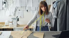 Young seamstress is checking clothing paper patterns and measuring them with tape-measure while looking at smart phone. Nice light studio with garments stock footage