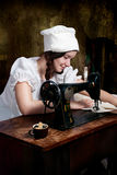 Young seamstress with old sewing machine Stock Photo