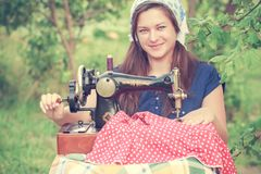 Young seamstress with vintage hand sewing machine Stock Images
