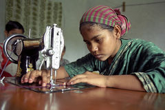 Young seamstress is working with sewing machine. Bangladesh, city Tangail: teenage girl in traditional colorful costume with headdress, is to work with an old Stock Image