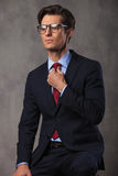 Young seated business man fixing his tie Royalty Free Stock Photography