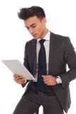 Young seated business man reading on his tablet Royalty Free Stock Photo