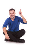 Young seated casual man pointing up Stock Photos