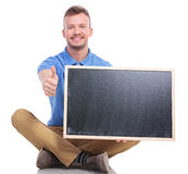 Young seated man with blackboard shows thumb up Royalty Free Stock Photos