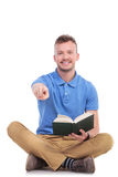 Young seated man with book points at you Stock Photo