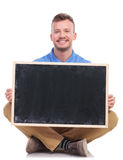 Young seated man holds a blank blackboard Stock Images