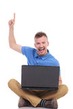 Young seated man with laptop points up. Casual young man holding his laptop while sitting on the floor with his feet crossed and pointing up with a smile on his Royalty Free Stock Photography