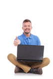 Young seated man with laptop show thumb up Royalty Free Stock Photos