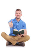 Young seated man shows thumb up. Casual young man sitting on the floor and holding a book while showing the thumb up gesture, with a smile on his face. on a Royalty Free Stock Photo