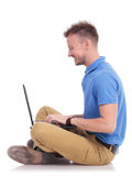 Young seated man works on laptop Stock Image