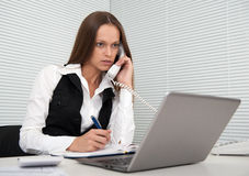 Young secretary answering telephone Royalty Free Stock Image