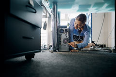 Young secretary connecting cables to pc in office Royalty Free Stock Image