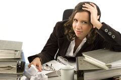 Young secretary with disorganized desktop. Young secretary looking at a desktop with files and papers Stock Photo