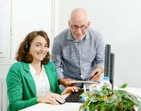 Young secretary and his boss in the office Royalty Free Stock Photos