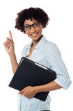 Young secretary holding file and pointing upwards Royalty Free Stock Images