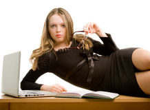 Young secretary lying on the table. Businesswoman lying on the desk royalty free stock image