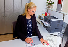 Young secretary in a office. Beautiful blond secretary in her office working on computer Stock Photography